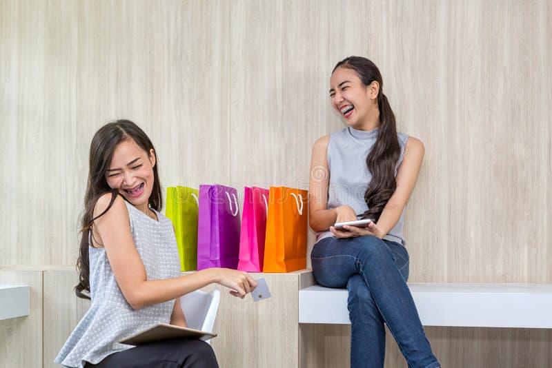 Due donne felici che usando acquisto sul telefono cellulare e sulla compressa Un acquisto sorridente di due giovani donne Lavoro  fotografia stock libera da diritti