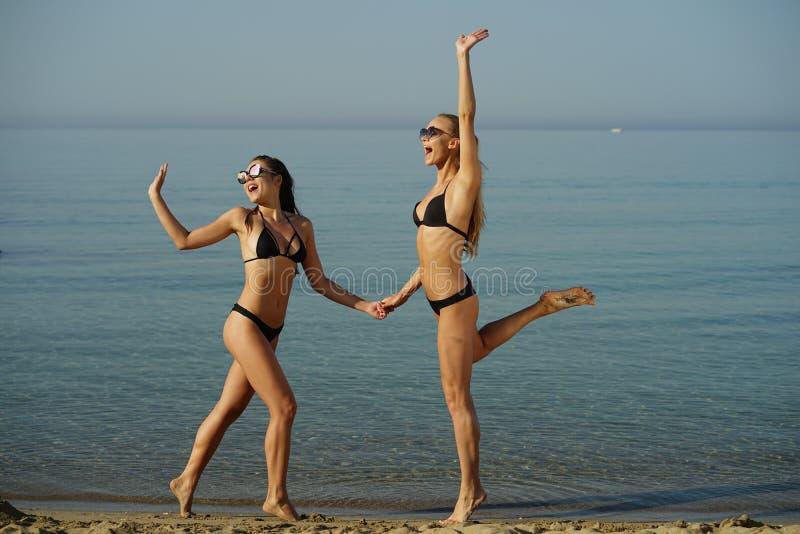 Due donne felici sulla spiaggia fotografie stock