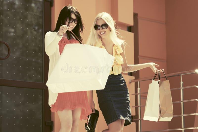 Due donne giovani di modo con i sacchetti della spesa accanto alla porta del centro commerciale immagini stock libere da diritti
