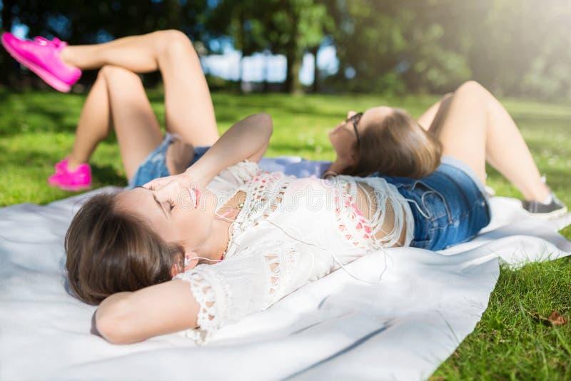 Due donne graziose che si rilassano alla musica d'ascolto del parco fotografia stock