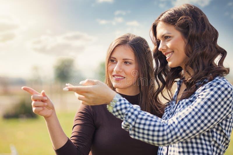 Due donne graziose in un parco i loro punti a qualcosa fotografia stock libera da diritti