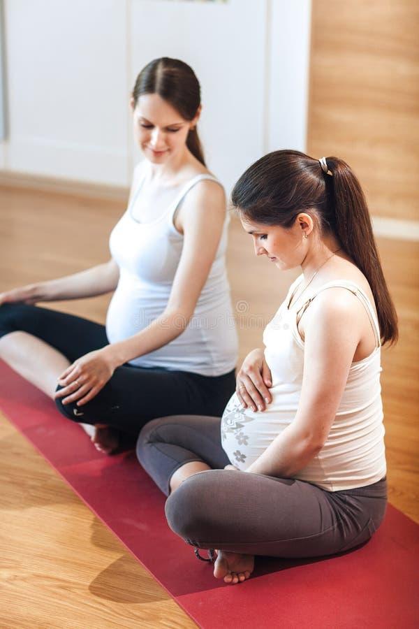 Due donne incinte stanno sedendo in una stanza di forma fisica in una posa di yoga, tenente le loro mani sulla loro pancia che se fotografie stock libere da diritti