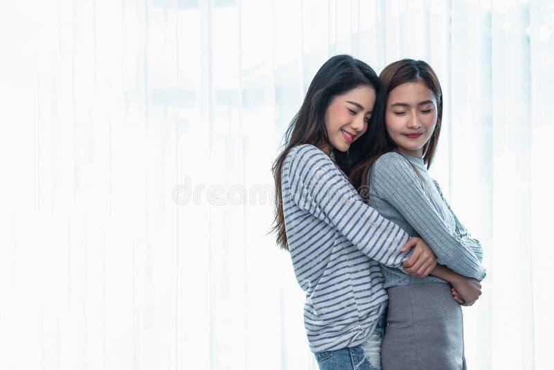 Due donne lesbiche asiatiche abbracciano ed abbracciando insieme nella camera da letto La gente delle coppie e concetto di bellez fotografia stock