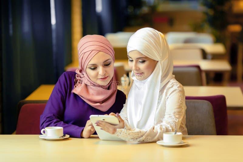 Due donne musulmane in un caffè, comperano online facendo uso della compressa elettronica fotografia stock libera da diritti