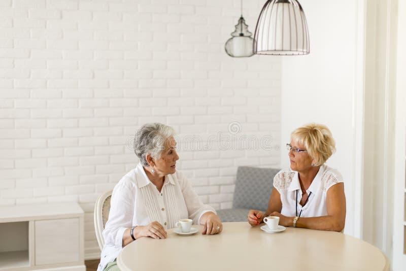 Due donne più anziane che bevono coffe a casa e conversazione fotografie stock