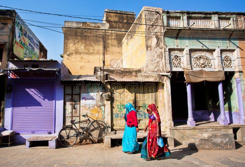 Due donne in sari che camminano giù la via immagine stock libera da diritti