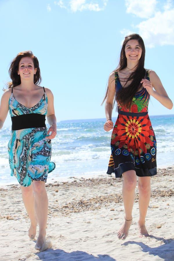 Due donne scalze attraenti sulla spiaggia fotografia stock libera da diritti