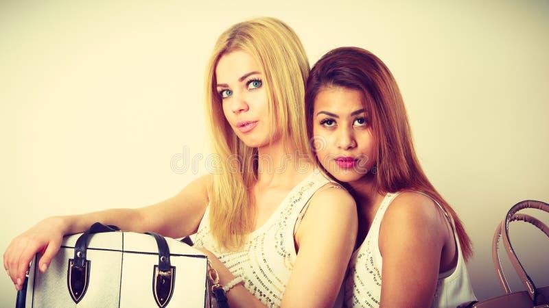 Due donne sedute sul divano a presentare le borse immagine stock