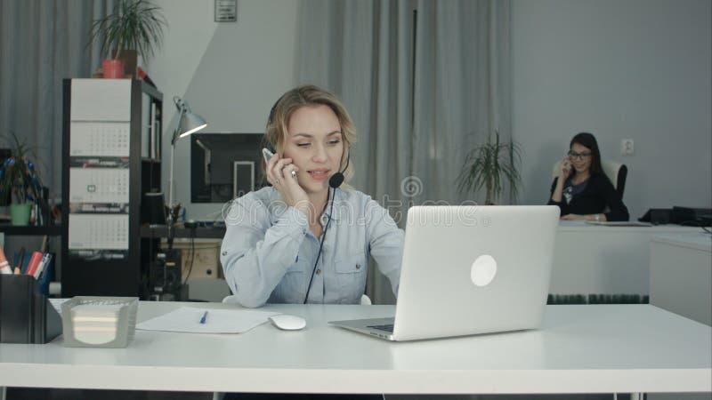 Due donne sorridenti che lavorano nelle telefonate di risposta di call-center immagine stock
