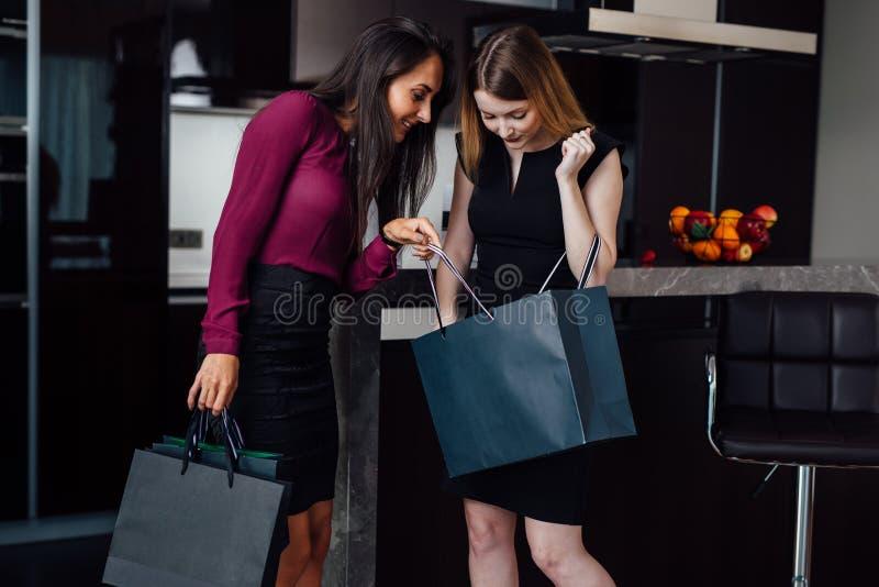 Due donne splendide dopo la compera a casa Una ragazza che mostra i suoi acquisti ad un amico femminile che sta a casa fotografie stock