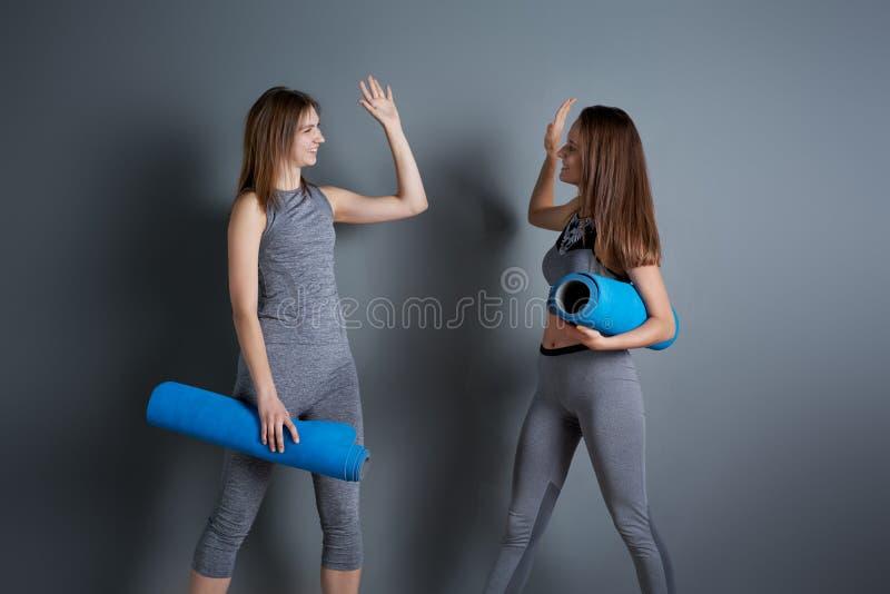 Due donne sporche fanno la stretta di mano mentre sono in piedi con tappeti blu avvolti contro il muro grigio vuoto fotografia stock