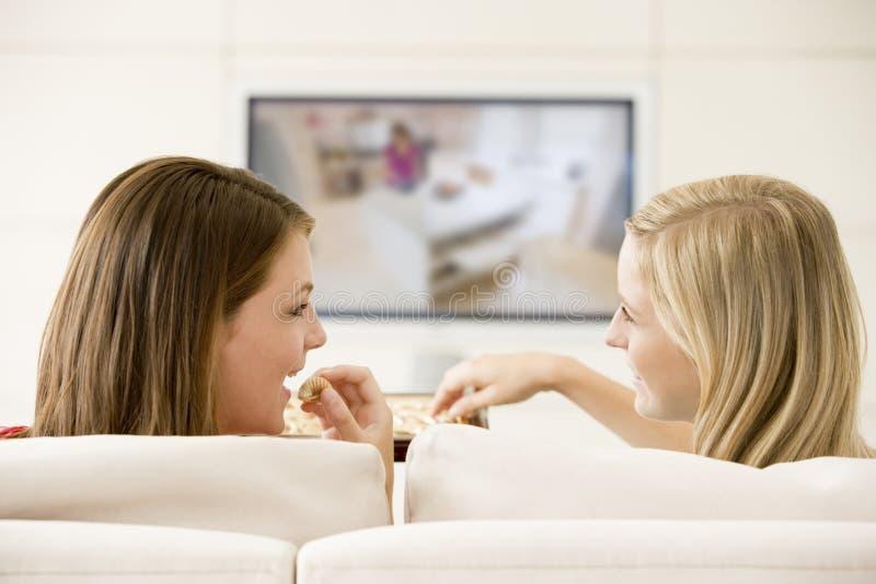 Due donne in televisione di sorveglianza del salone fotografia stock