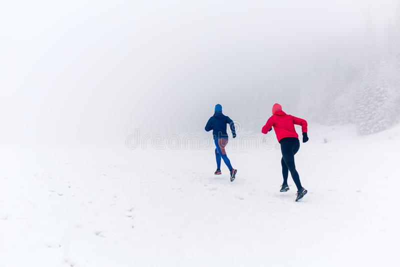 Due donne trascinano il funzionamento sulla neve in montagne dell'inverno fotografie stock