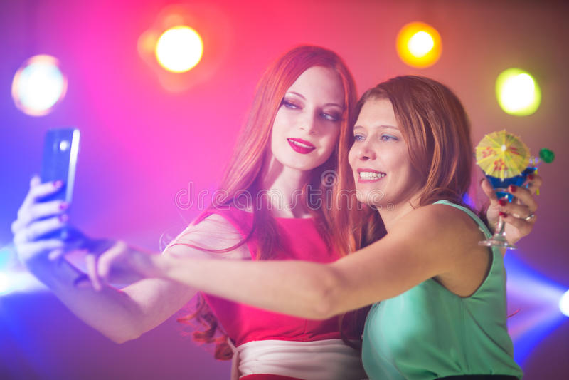 Due donne in un night-club sotto il riflettore con un cocktail dentro immagini stock