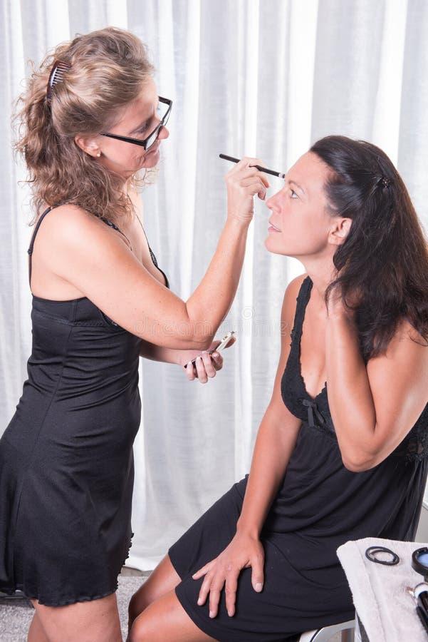 Due donne, una sta mettendo l'altra compongono sopra fotografie stock libere da diritti