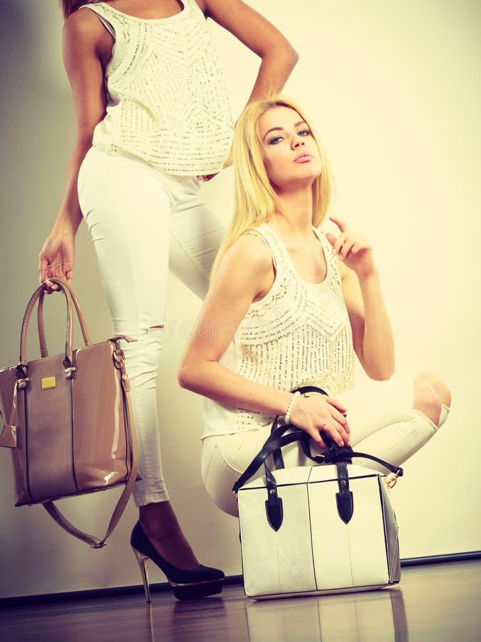 Due donne in vestiti bianchi con le borse delle borse immagini stock libere da diritti