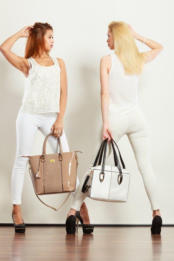 Due donne in vestiti bianchi con le borse delle borse immagine stock libera da diritti