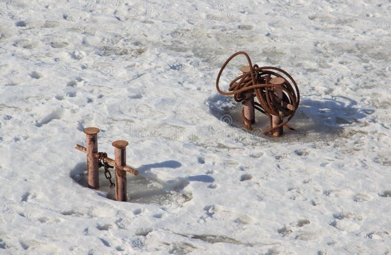 Due doppie bitte di bitta con la catena ed il metallo rope in fiume congelato immagini stock libere da diritti