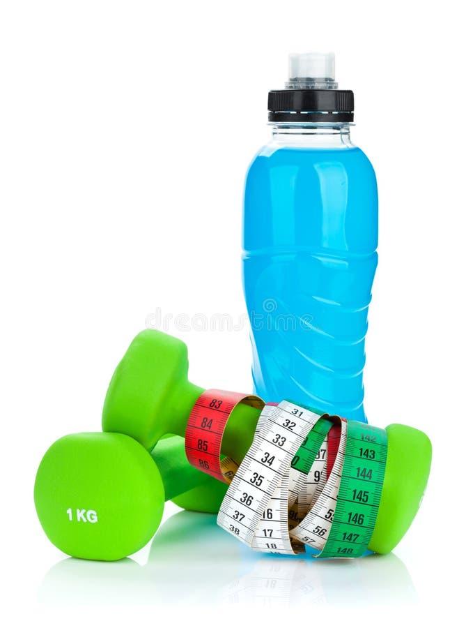 Due dumbells, misura di nastro e bottiglie verdi della bevanda Forma fisica e h fotografia stock libera da diritti