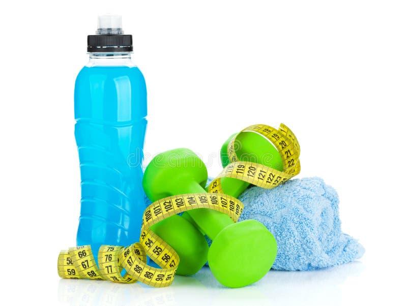 Due dumbells, misura di nastro e bottiglie verdi della bevanda Forma fisica e h immagine stock libera da diritti