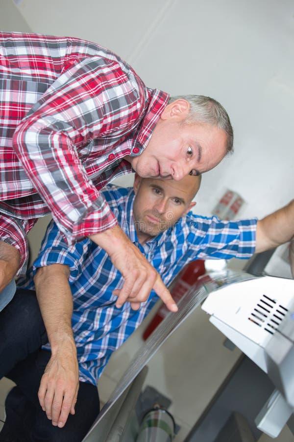 Due elettricisti che riparano i dispositivi fotografia stock libera da diritti