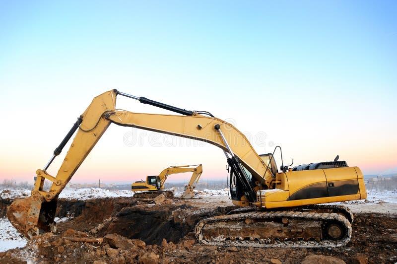 Due escavatori del caricatore in a cielo aperto in inverno immagini stock