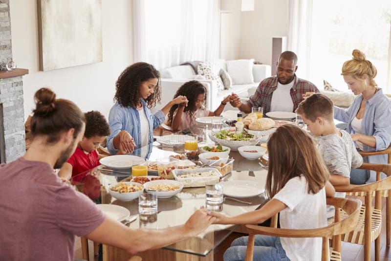 Due famiglie che pregano prima del godere del pasto a casa insieme fotografie stock libere da diritti