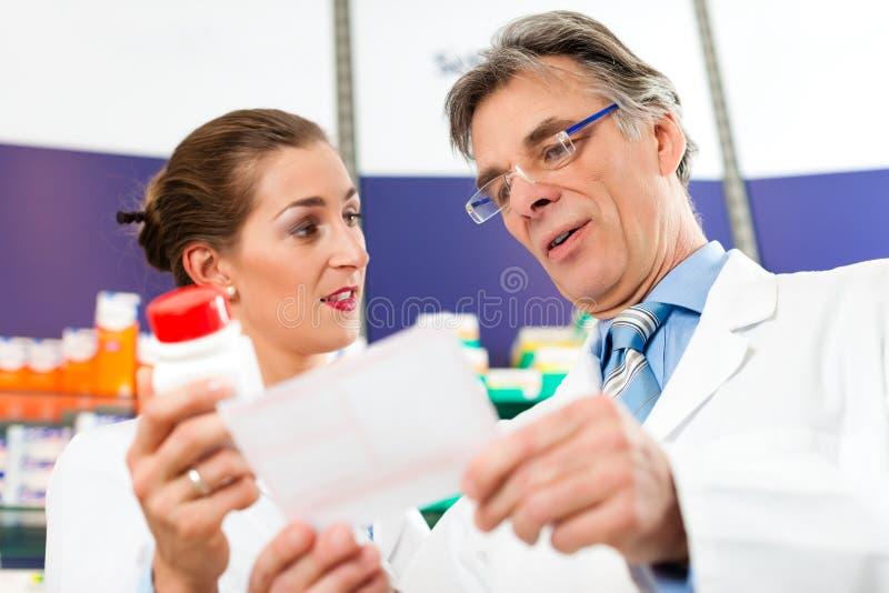 Due farmacisti nel consulto della farmacia fotografia stock libera da diritti