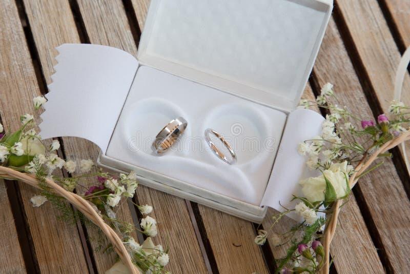 Due fedi nuziali in cassa bianca nel fondo di legno con i fiori fotografie stock