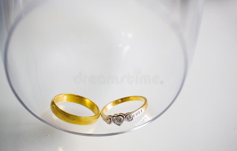 due fedi nuziali del diamante per lo sposo e la sposa con la collana della perla su fondo bianco, simbolo di nozze immagine stock