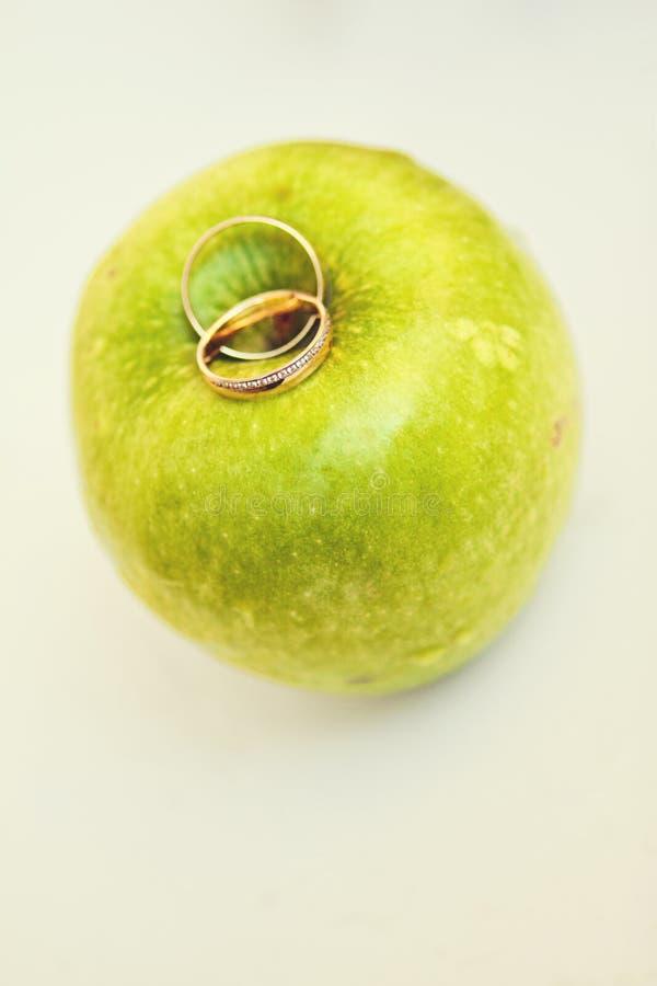 Due fedi nuziali dell'oro con un diamante sulla mela verde su un fondo bianco fotografia stock