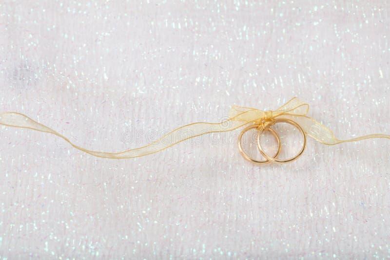 Due fedi nuziali dorate legate con un nastro dorato su fondo brillante bianco fotografie stock