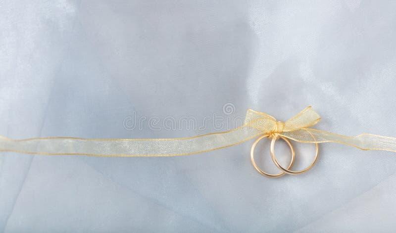 Due fedi nuziali dorate legate con un nastro dorato su fondo brillante d'argento fotografia stock