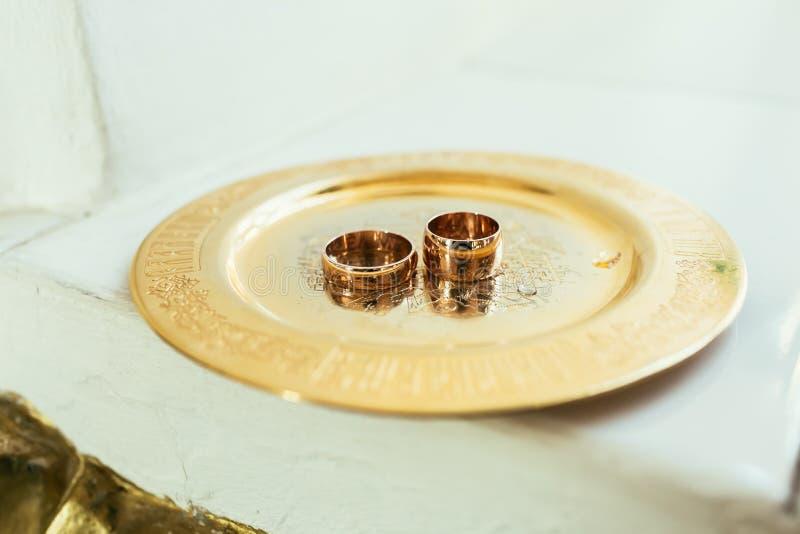 Due fedi nuziali pesanti dell'oro su una cerimonia di nozze nella chiesa fotografia stock libera da diritti