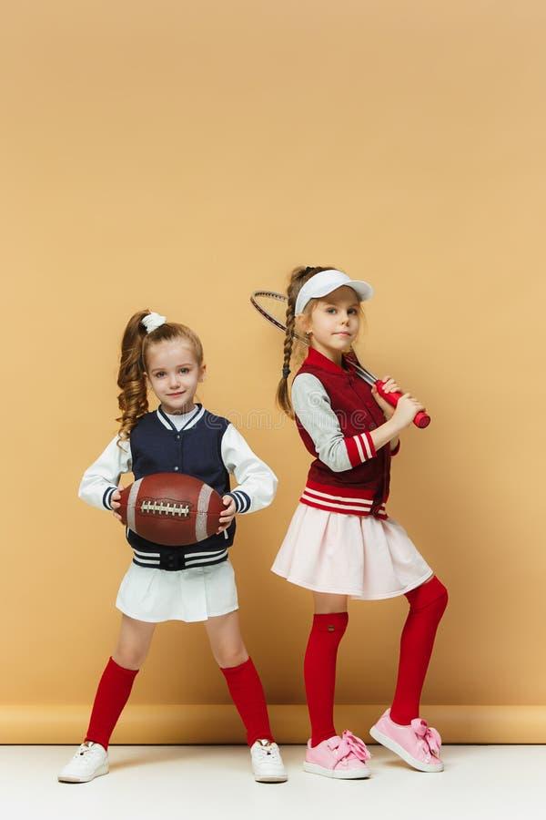 Due felici ed i bambini beautyful mostrano lo sport differente Concetto di modo dello studio Concetto di emozioni immagine stock