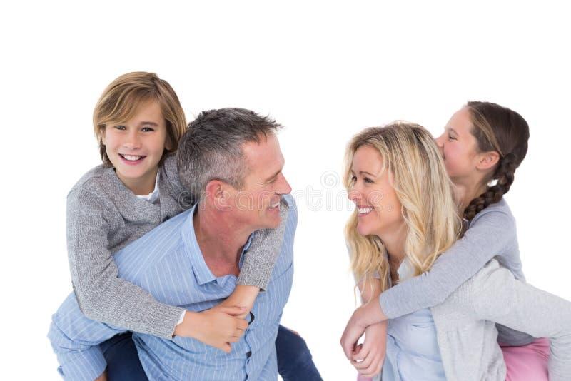 Due felici parent dare ai loro bambini un a due vie immagini stock libere da diritti
