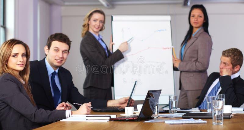 Due femmine presentano il grafico su flipchart immagini stock libere da diritti