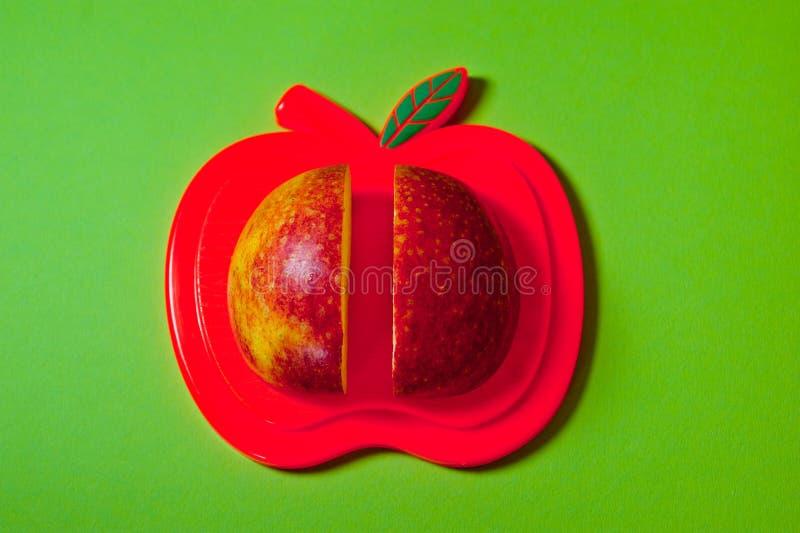 Due fette di mela rossa che si trovano su un colpo del tagliere grande contro un fondo arancio immagini stock libere da diritti