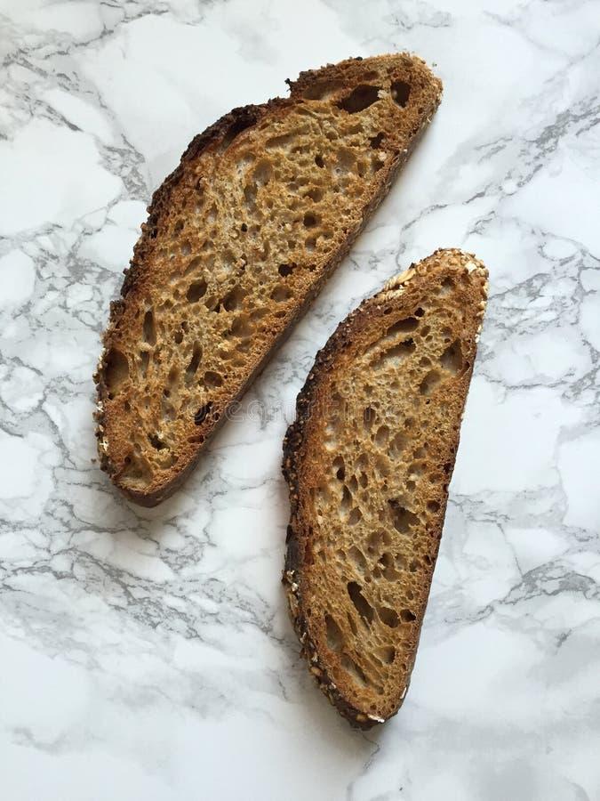 Due fette di pane integrale artigianale del lievito naturale sul controsoffitto di marmo immagini stock libere da diritti