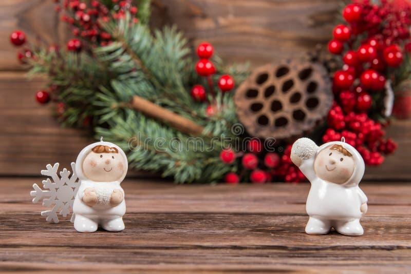 Due figure dei bambini che giocano le palle di neve su un fondo strutturato di legno scuro Giocattoli e fiocchi di neve di Natale immagine stock