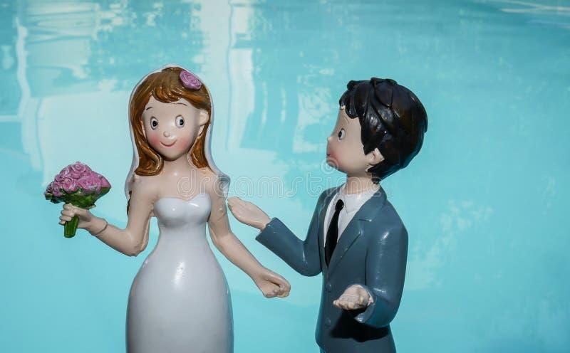 Due figurine, il marito e la moglie, il giorno del matrimonio, bagnarsi in acqua come per un rituale d'amore immagini stock