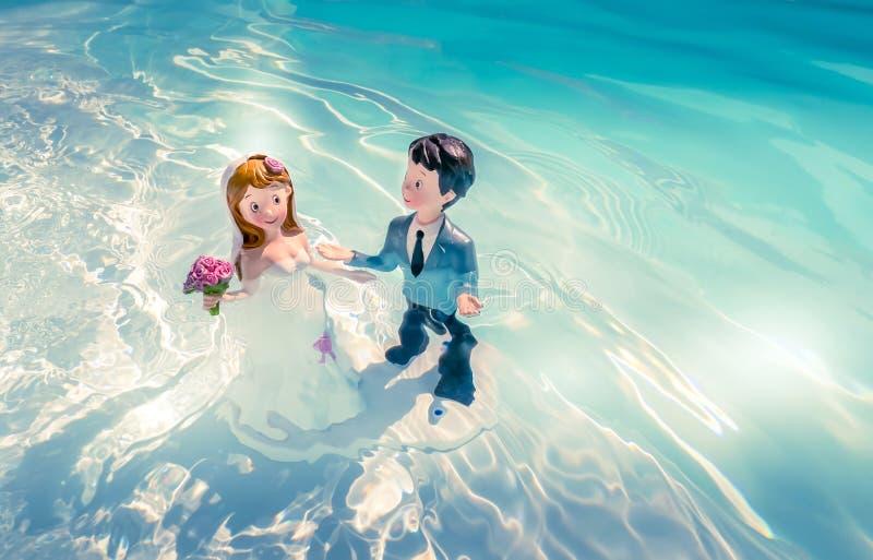 Due figurine, il marito e la moglie, il giorno del matrimonio, bagnarsi in acqua come per un rituale d'amore immagine stock