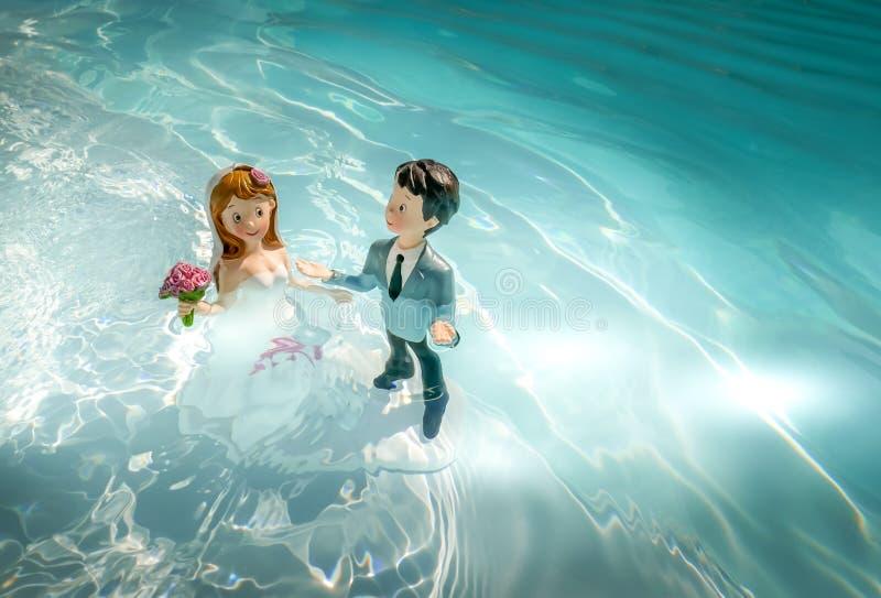Due figurine, il marito e la moglie, il giorno del matrimonio, bagnarsi in acqua come per un rituale d'amore fotografie stock libere da diritti