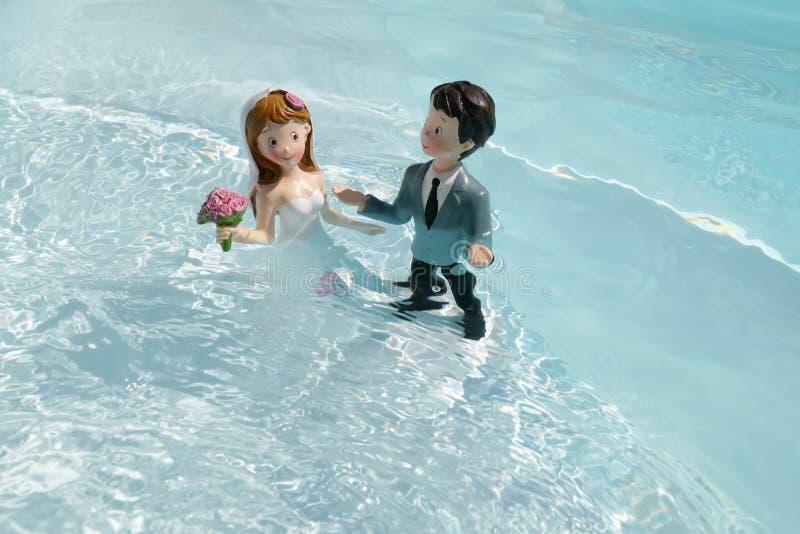 Due figurine, il marito e la moglie, il giorno del matrimonio, bagnarsi in acqua come per un rituale d'amore fotografie stock