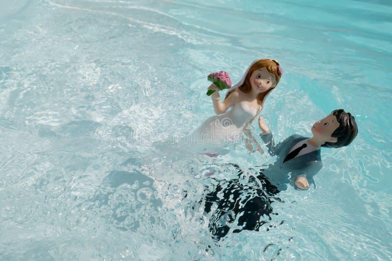 Due figurine, il marito e la moglie, il giorno del matrimonio, bagnarsi in acqua come per un rituale d'amore fotografia stock libera da diritti