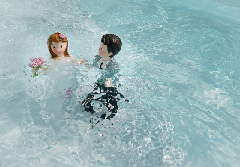 Due figurine, il marito e la moglie, il giorno del matrimonio, bagnarsi in acqua come per un rituale d'amore fotografia stock