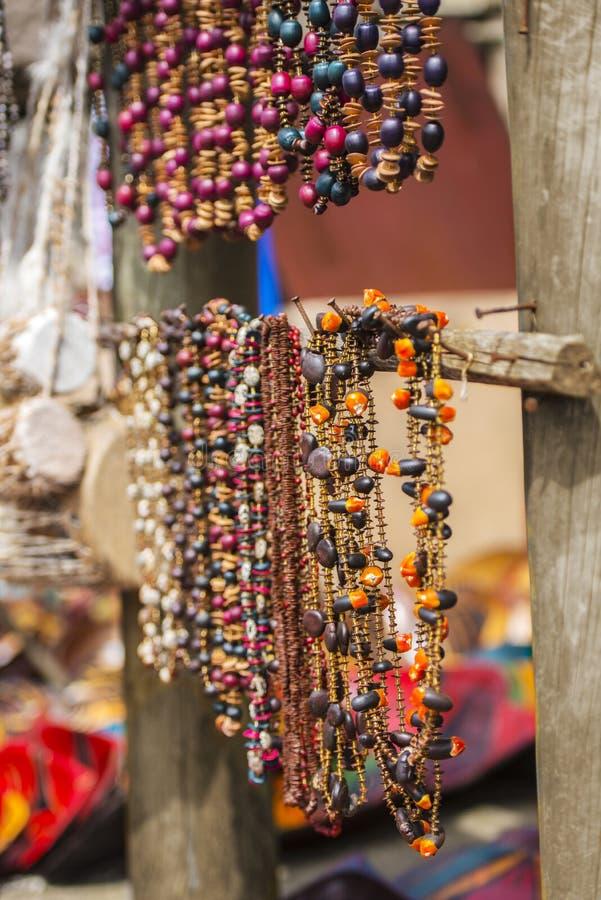 Due file di belle collane africane della perla che pendono dai rami di legno in un mercato dell'aria aperta immagine stock