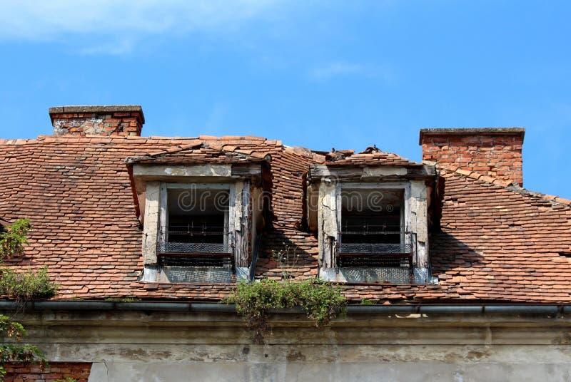 Due finestre distrutte del tetto con i supporti arrugginiti del fiore del metallo su vecchia costruzione abbandonata con le matto fotografia stock