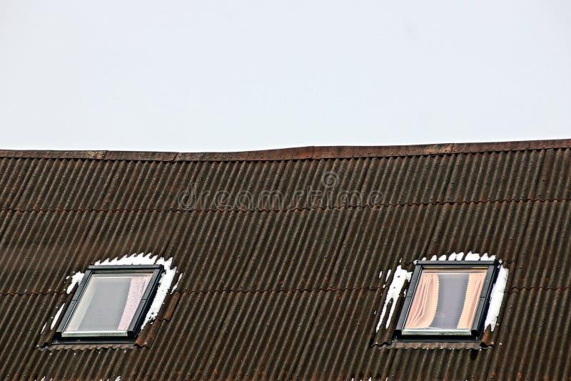 Due finestre nella neve su un tetto di ardesia contro il cielo immagine stock
