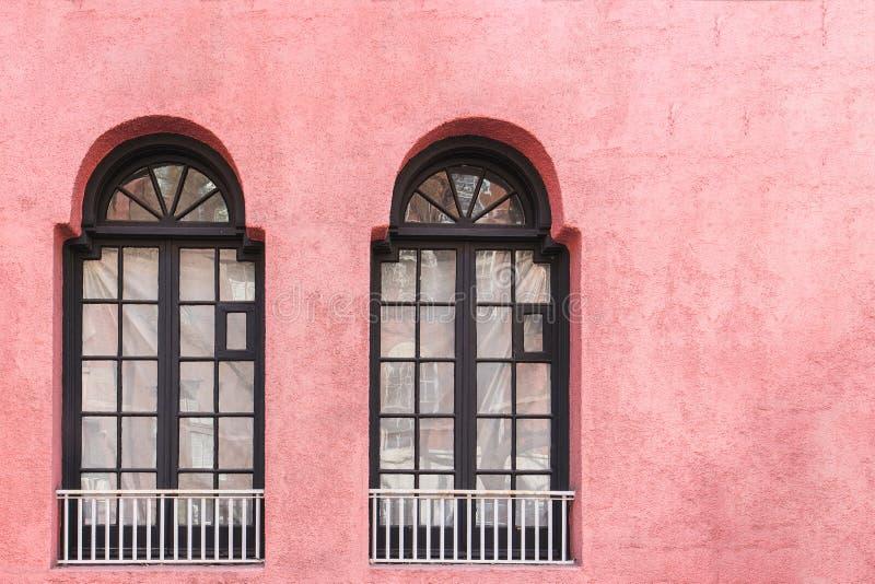 Due finestre nere classiche sulla parete rosa con lo spazio della copia fotografia stock libera da diritti